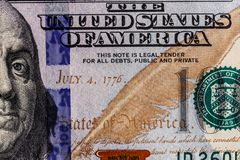 Closeup of Ben Franklin and the date of independence July 4, 1776 on a one hundred dollar bill for background VII. Closeup of Ben Franklin and the date of royalty free stock photo