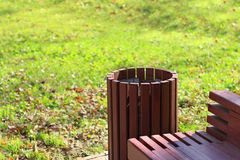 Closeup of bench and garbage can in park Stock Photo