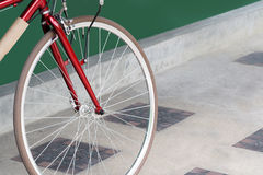 Closeup bicycle wheels on the cement floor. And close to the green flap Stock Photo