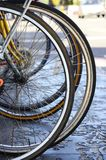 Bicycle wheels, detail. Closeup of bicycle wheels - parked bicycles being used as a urban transportation medium for a greener environment Royalty Free Stock Image