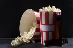 Closeup of big buckets of popcorn on the dark surface agains black wall