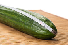 Closeup with a big cucumber and a centimeter. Closeup with a big green cucumber and a white centimeter on a bamboo plate royalty free stock photos