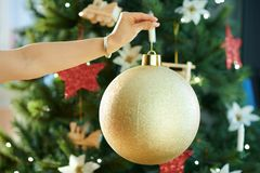 Closeup on big gold Christmas ball in a hand of woman stock photos