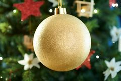 Closeup on big gold Christmas ball near Christmas tree royalty free stock photos