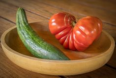 Big red heart-shaped tomato and cucumber in a wooden bowl. Closeup of a big red heart-shaped tomato and cucumber in a wooden bowl stock photography