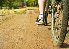 Closeup of  bike on dirt track. Focus on foot Royalty Free Stock Image