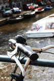 Closeup of bike handles with tour boat passing behind. Part of a bike that is locked to a bridge rail, with a tour boat passing underneath the bridge Royalty Free Stock Images