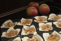 Closeup of biscuits in pan before baking with red apples in background Royalty Free Stock Images