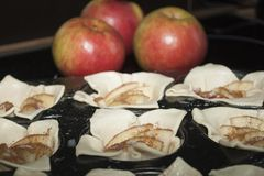 Closeup of biscuits in pan before baking with red apples in background Stock Photography