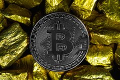 Closeup of bitcoin digital currency and gold nugget or gold ore on black background, precious stone or lump of golden stone,. Cryptocurrency money financial and stock images