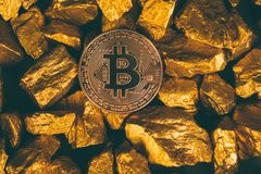 Closeup of bitcoin digital currency and gold nugget or gold ore on black background, precious stone or lump of golden stone,. Cryptocurrency money financial and royalty free stock images