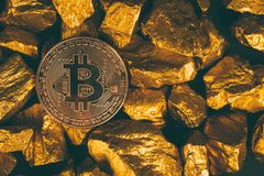 Closeup of bitcoin digital currency and gold nugget or gold ore on black background, precious stone or lump of golden stone,. Cryptocurrency money financial and stock image
