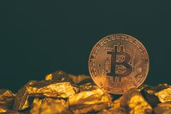 Closeup of bitcoin digital currency and gold nugget or gold ore on black background, precious stone or lump of golden stone,. Cryptocurrency money financial and royalty free stock image