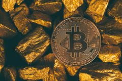 Closeup of bitcoin digital currency and gold nugget or gold ore on black background, precious stone or lump of golden stone,. Cryptocurrency money financial and royalty free stock photos