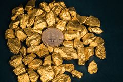 Closeup of bitcoin digital currency and gold nugget or gold ore on black background, precious stone or lump of golden stone,. Cryptocurrency money financial and stock photo