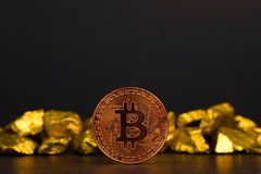 Closeup of bitcoin digital currency and gold nugget or gold ore on black background, precious stone or lump of golden stone,. Cryptocurrency money financial and royalty free stock photo