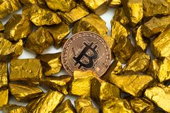 Closeup of bitcoin digital currency and gold nugget or gold ore on white background, precious stone or lump of golden stone,. Cryptocurrency money financial and stock image