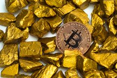 Closeup of bitcoin digital currency and gold nugget or gold ore on white background, precious stone or lump of golden stone,. Cryptocurrency money financial and stock photo