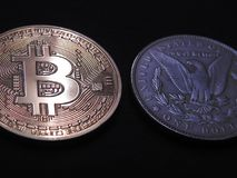 Bitcoin and antique Silver Morgan Dollar. Closeup of Bitcoin and one antique old Silver Morgan Dollar on black Background royalty free stock images