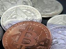 Bitcoin and Silver Morgan Dollars. Closeup of Bitcoin on top of a few Silver Morgan Dollars on Black Background royalty free stock photography