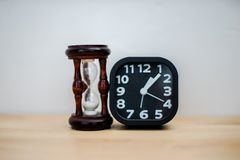 Closeup black alarm clock for decorate next to hourglass, wooden desk front concrete wall background. royalty free stock image