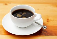 Closeup of black coffee in cup. Closeup of black coffee in a white cup. Shot on light wood background Stock Photography