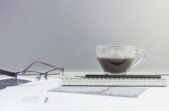 Closeup black coffee in cup of coffee on note book and pencil with work paper on blurred wooden desk and glass wall textured backg Stock Photos