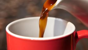 Closeup. Black coffee poured from coffeepot in red small cup stock video footage