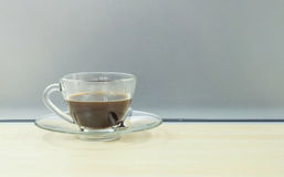 Closeup black coffee in transparent cup of coffee on blurred wooden desk and frosted glass wall textured background Royalty Free Stock Images
