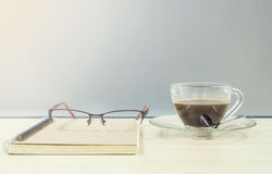 Closeup black coffee in transparent cup of coffee brown note book with glasses on blurred wooden desk and frosted glass wall textu Stock Images