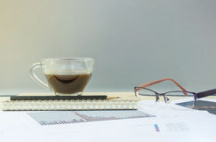 Closeup black coffee in transparent cup of coffee on note book and pencil with work paper on blurred wooden desk and glass wall te Royalty Free Stock Photos