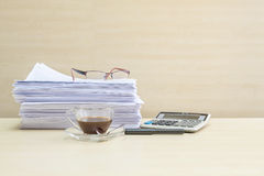 Closeup black coffee in transparent cup of coffee with pile of work paper and calculator on blurred wooden desk and wall textured. Black coffee in transparent Stock Photography