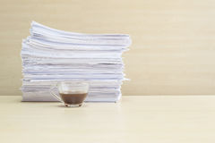 Closeup black coffee in transparent cup of coffee and pile of work paper in work concept on blurred wooden desk and wall textured. Black coffee in transparent Stock Image