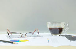 Closeup black coffee in transparent cup of coffee with work paper on blurred wooden desk and frosted glass wall textured backgroun. Black coffee in transparent Stock Images