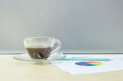 Closeup black coffee in transparent cup of coffee with work paper and pencil on blurred wooden desk and frosted glass wall texture Royalty Free Stock Photos