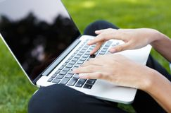 Happy young woman using laptop outdoors. Closeup of black female hands working on laptop with blanck screen for copy space. Technology, education, advertising Royalty Free Stock Photo
