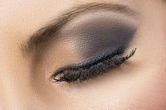 Closeup of black and gold smokey eye Stock Photos