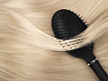 Black hair brush and blond hair.