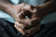 Closeup of black hands grabbed together stock photography