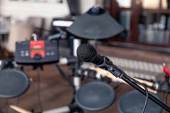 Closeup black iron microphone stands on stage background of installation of musical cymbals. Concept live concert in bar in. Closeup black iron microphone stands stock photography