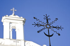 Closeup of black metal cross with a white church in the background Stock Photo