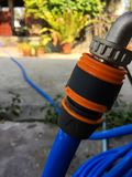 Blue garden water hose nozzle and orange connector stock photo