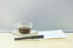 Closeup black pen on white book with black coffee in transparent cup of coffee on blurred wooden desk and frosted glass wall textu Stock Image