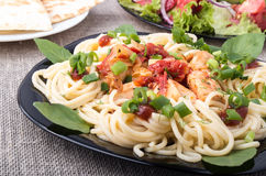 Closeup black plate with pasta and slices of braised chicken Royalty Free Stock Photos