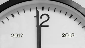 One minute to midnight and the new year. Closeup on the black pointers of a white background round clock marking a minute before midnight, marking the end of Royalty Free Stock Photos