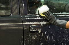 Closeup black rubber gloves working on washing car door window with soapy water Stock Image