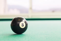 Closeup black snooker billards ball on table with green surface. Closeup on black snooker pool billards ball on table with green surface Stock Image
