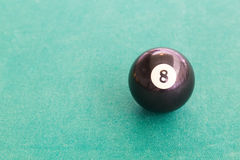 Closeup black snooker billards ball on table with green surface. Closeup on black snooker pool billards ball on table with green surface Stock Images