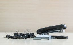 Closeup black stapler and black stamp paper clip , office equipment on blurred wood desk and wall in office room textured backgrou. Nd Royalty Free Stock Photo
