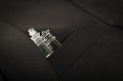 Closeup black suit jacket chest pocket with glass chess piece sitting inside.  Royalty Free Stock Photo